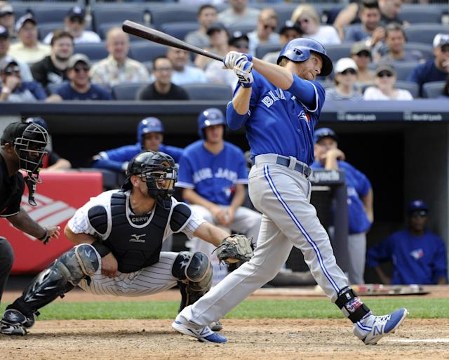 Toronto Blue Jay' Dan Johnson, right, hits a three-run home run as New York Yankees catcher Francisco Cervelli, left, looks on during the ninth inning of a baseball game on Saturday, July 26, 2014, at Yankee Stadium in New York. The Blue Jays won 6-4. (AP Photo/Bill Kostroun)