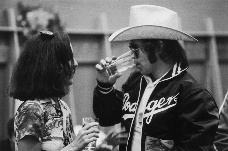 <p>Elton John chats with music journalist Lisa Robinson after a concert on the the Rolling Stones' Tour of the Americas in 1975.</p>