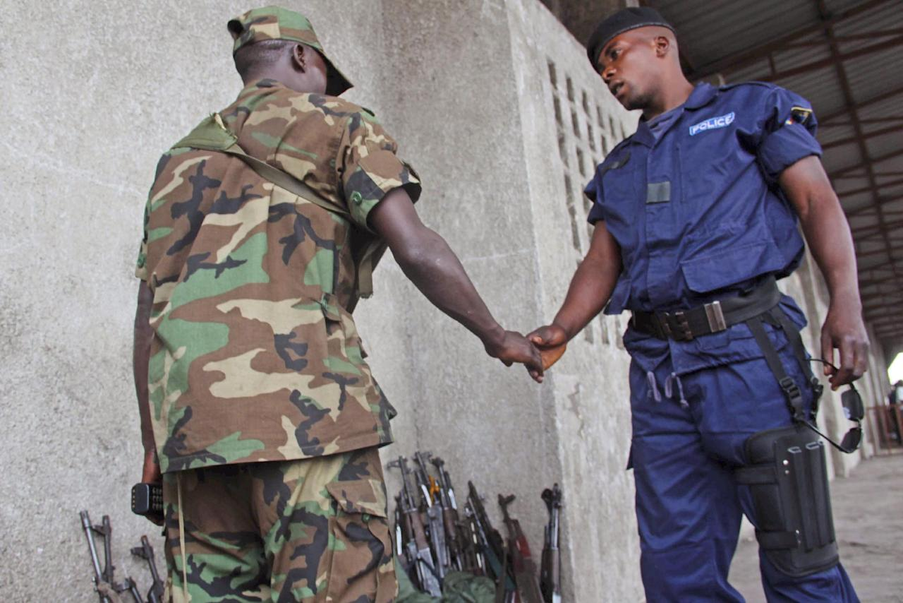 A Congo government policeman shake hands with an M23 rebel, after he and other policemen handed their weapons in to M23 rebels during a M23 rally in Goma, Congo, Wednesday, Nov. 21, 2012. A rebel group believed to be backed by Rwanda seized the strategic, provincial capital of Goma in eastern Congo on Tuesday, home to more than 1 million people as well as an international airport in a development that threatens to spark a new, regional war, officials and witnesses said. (AP Photo/Melanie Gouby)