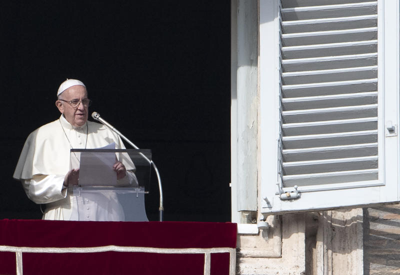 Pope Francis addresses the crowd from the window of the apostolic palace overlooking Saint Peter's square during his Sunday Angelus prayer on Dec. 2. (TIZIANA FABI via Getty Images)