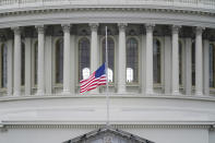 FILE - In this Jan. 8, 2021 file photo, an American flag flies at half-staff in remembrance of U.S. Capitol Police Officer Brian Sicknick above the Capitol Building in Washington. (AP Photo/Patrick Semansky)