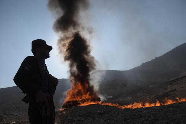 <p>An Afghan policeman watches as a cache of alcohol and drugs burns on the outskirts of Kabul on December 20, 2016.<br> Ninety eight tons of opium, heroin, hashish and alcoholic drinks were set on fire, officials said. (Photo: Shah Marai/ AFP/Getty Images) </p>
