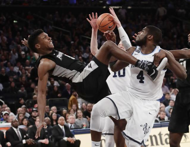 Providence's Rodney Bullock (5) falls as Villanova's Eric Paschall (4) blocks his shot during the second half of an NCAA college basketball game in the Big East men's tournament final Saturday, March 10, 2018, in New York. (AP Photo/Frank Franklin II)