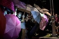 Pro-democracy protesters stand behind umbrellas as police advance, Hong Kong on October 15, 2014 (AFP Photo/Alex Ogle)