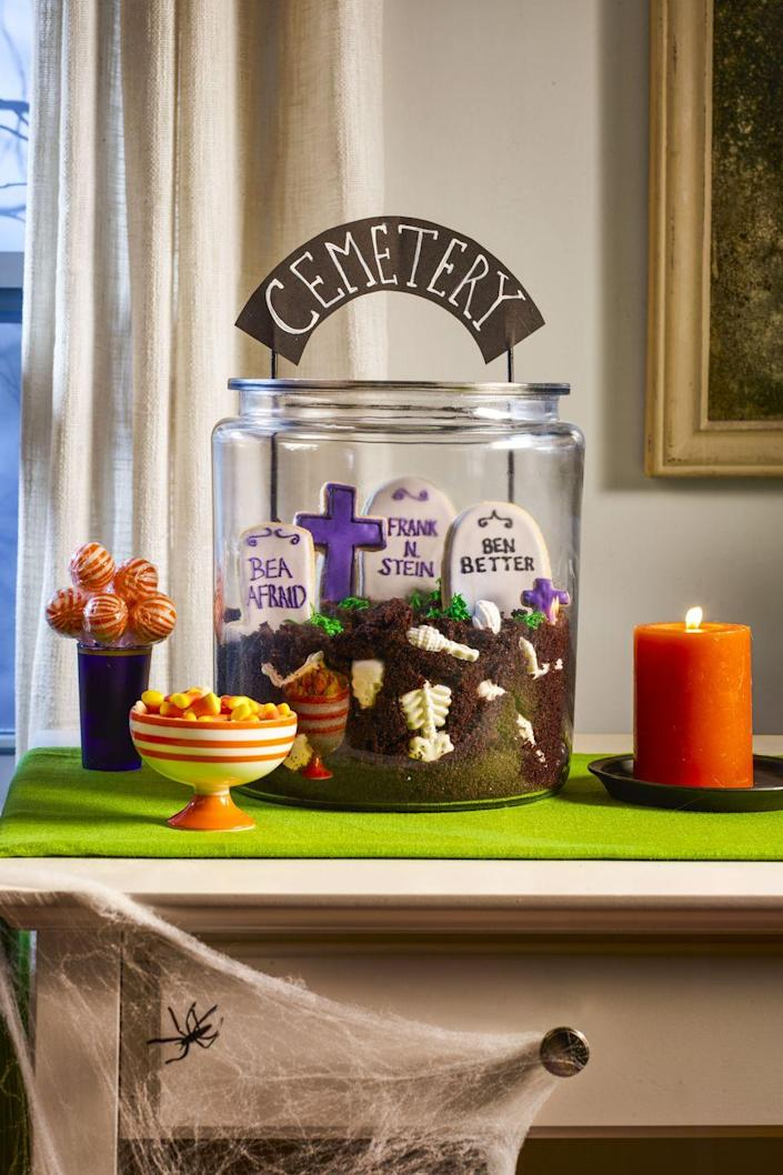 """<p>This is one dessert you'll be dying to dig into! Fill a large glass cookie jar chocolate cake crumbs and <a href=""""https://www.amazon.com/Halloween-Silicone-Skeleton-Decoration-Decorate/dp/B08HRXJXJB?tag=syn-yahoo-20&ascsubtag=%5Bartid%7C10070.g.2586%5Bsrc%7Cyahoo-us"""" rel=""""nofollow noopener"""" target=""""_blank"""" data-ylk=""""slk:white chocolate bones"""" class=""""link rapid-noclick-resp"""">white chocolate bones</a>. Use a <a href=""""https://www.amazon.com/Tombstone-Cookie-Cutter-Stainless-Steel/dp/B07HLVMBV7/?tag=syn-yahoo-20&ascsubtag=%5Bartid%7C10070.g.2586%5Bsrc%7Cyahoo-us"""" rel=""""nofollow noopener"""" target=""""_blank"""" data-ylk=""""slk:tombstone cookie cutter"""" class=""""link rapid-noclick-resp"""">tombstone cookie cutter</a> to make sugar cookies and decorate with royal icing. Pipe in tufts of grass using green-tinted <a href=""""https://www.womansday.com/food-recipes/food-drinks/recipes/a10410/buttercream-frosting-recipe-122427/"""" rel=""""nofollow noopener"""" target=""""_blank"""" data-ylk=""""slk:buttercream"""" class=""""link rapid-noclick-resp"""">buttercream</a>, then push a DIY cemetery sign made from card stock and painted wood skewers for a finishing touch.</p><p><a href=""""https://www.womansday.com/food-recipes/food-drinks/recipes/a12008/basic-sugar-cookies-recipe-wdy1212/"""" rel=""""nofollow noopener"""" target=""""_blank"""" data-ylk=""""slk:Get the Basic Sugar Cookie recipe."""" class=""""link rapid-noclick-resp""""><strong><em>Get the Basic Sugar Cookie recipe.</em></strong></a></p>"""
