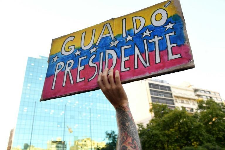 "A protester holds a sign in favor of Juan Guaido, the self-declared ""interim president"" of Venezuela, during a demonstration against Venezuelan President Nicolas Maduro in Montevideo, Uruguay on February 7, 2019"