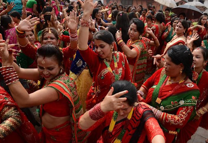 Nepalese Hindu women, dressed in red, dance after paying homage to Shiva, the Hindu god of destruction as they celebrate the Teej festival at the Pashupatinath temple area in Kathmandu on September 16, 2015 (AFP Photo/Prakash Mathema)