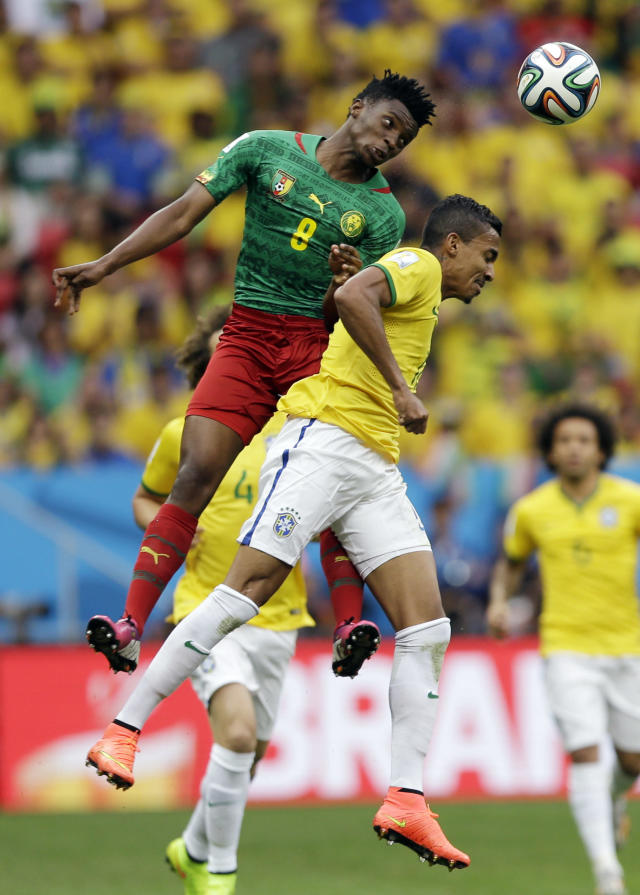 Cameroon's Benjamin Moukandjo, left, and Brazil's Luiz Gustavo go for a header during the group A World Cup soccer match between Cameroon and Brazil at the Estadio Nacional in Brasilia, Brazil, Monday, June 23, 2014. (AP Photo/Andre Penner)