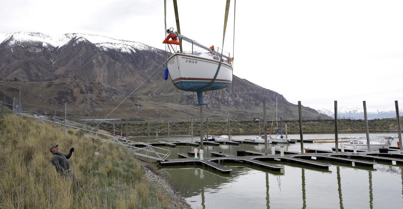 A sailboat is hoisted into the Great Salt Lake Thursday, April 6, 2017, about 20 miles west of Salt Lake City. Dozens of beached sailboats that spent two years on the shore of Utah's drought-stricken Great Salt Lake were hoisted on cranes back into the briny waters after winter storms raised lake levels. (AP Photo/Rick Bowmer)