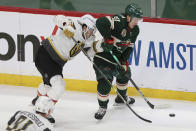 Minnesota Wild's Kirill Kaprizov (97) handles the puck next to Vegas Golden Knights' Mattias Janmark (26) during the third period in Game 3 of a first-round NHL hockey playoff series Thursday, May 20, 2021, in St. Paul, Minn. The Golden Knights won 5-2. (AP Photo/Stacy Bengs)
