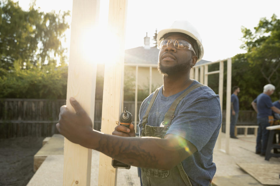 Man using power drill, working at construction site