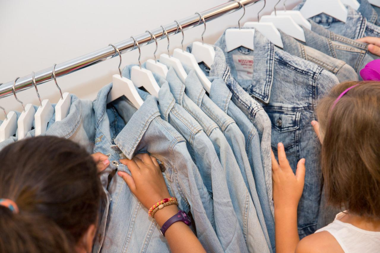 <p>Campers browse the racks for the perfect denim shirt to embroider.</p>