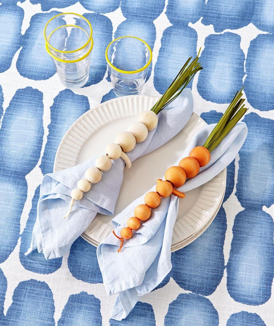 """<p>Made from mini wooden craft beads, these napkin rings mimic bunnies favorite foods, root veggies!</p><p><strong>To make:</strong> Dye wooden craft beads orange or white. Arrange eight beads small to large in a row, and thread a piece of twine in a corresponding color through beads; knot on both ends. Wrap a wooden craft ring with twine, and tie between the beads for the napkin holder. For the stems, attach lengths of preserved grass or green crepe paper to the top with hot-glue.</p><p><a class=""""link rapid-noclick-resp"""" href=""""https://www.amazon.com/Natural-Unfinished-Suitable-Holiday-Jewelry/dp/B08KD9R28B/ref=sr_1_5?tag=syn-yahoo-20&ascsubtag=%5Bartid%7C10050.g.1111%5Bsrc%7Cyahoo-us"""" rel=""""nofollow noopener"""" target=""""_blank"""" data-ylk=""""slk:SHOP WOODEN BEADS"""">SHOP WOODEN BEADS</a></p>"""