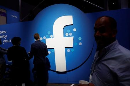 Attendees walk past a Facebook logo during Facebook Inc's F8 developers conference in San Jose