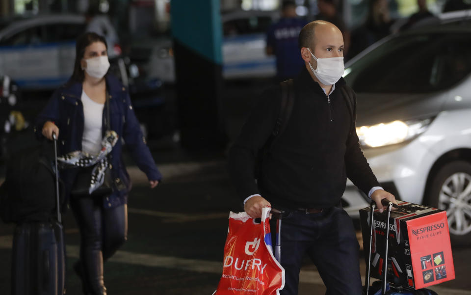 Passengers wearing masks as a precaution against the spread of the new coronavirus COVID-19 arrive to the Sao Paulo International Airport in Sao Paulo, Brazil, Wednesday, Feb. 26, 2020. (AP Photo/Andre Penner)