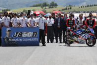 Teammates of 19 years-old Swiss pilot Jason Dupasquier stand near his motorbike, right, as they pay a minute of silence in his memory prior to the start of the Motogp Grand Prix of Italy at the Mugello circuit, in Scarperia, Italy, Sunday, May 30, 2021. Dupasquier died Sunday after being hospitalized Saturday, at the Florence hospital following his crash during the qualifying practices of the Moto3. (AP Photo/Antonio Calanni)
