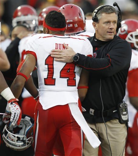 Utah head coach Kyle Whittingham, right, congratulates kick returner Reggie Dunn after his return for a touchdown against Colorado in the fourth quarter of Utah's 42-35 victory in an NCAA football game in Boulder, Colo., on Friday, Nov. 23, 2012. (AP Photo/David Zalubowski)