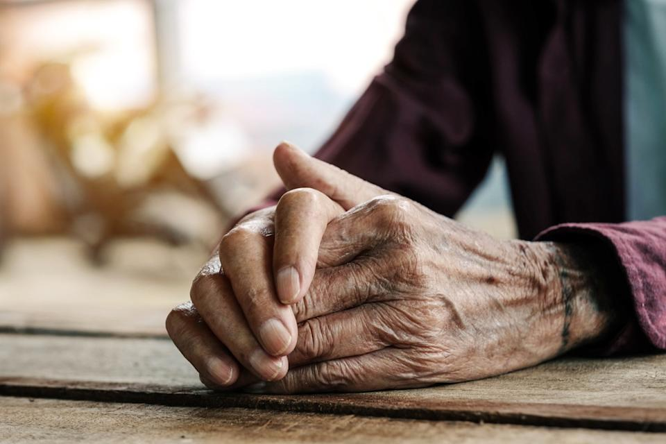Hands of an old man on the wood table.vintage tone - Image