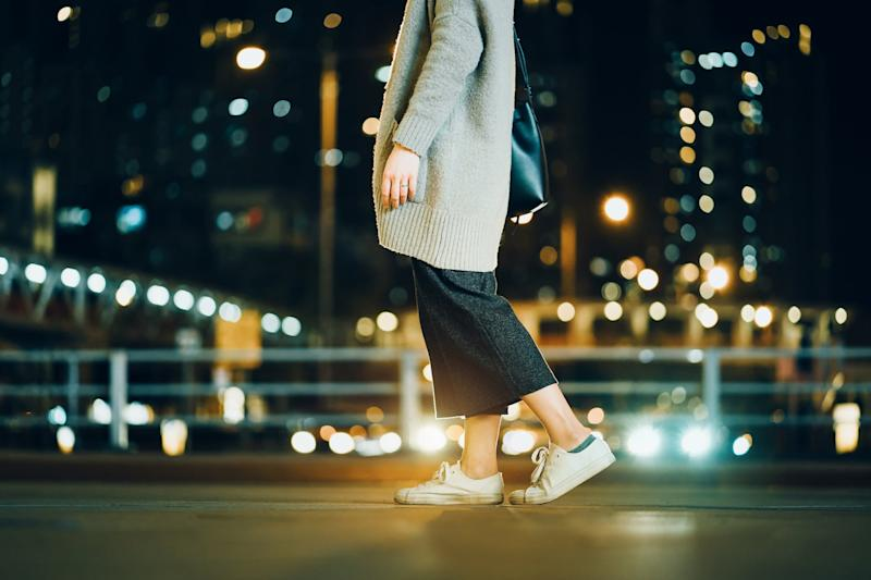 Cropped image of woman walking in the illuminated urban city at night