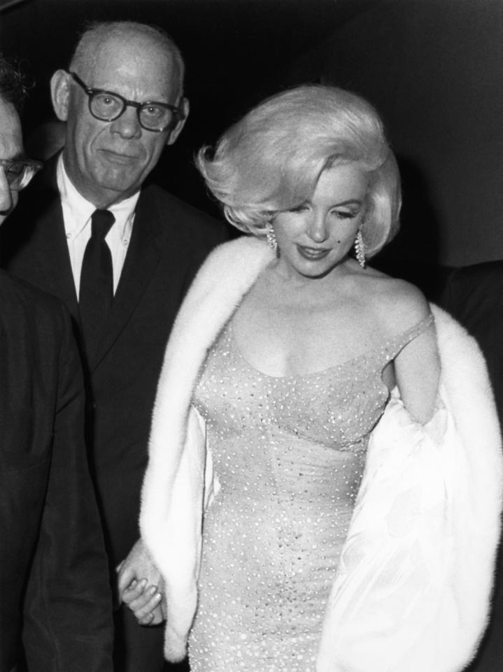 In this May 19, 1962 publicity photo provided by Running Press, actress Marilyn Monroe, right, arrives at Madison Square Garden to perform at a 45th birthday gala for President John F. Kennedy, in New York. She is escorted by her former father in law, Isidore Miller. (AP Photo/Courtesy Running Press)