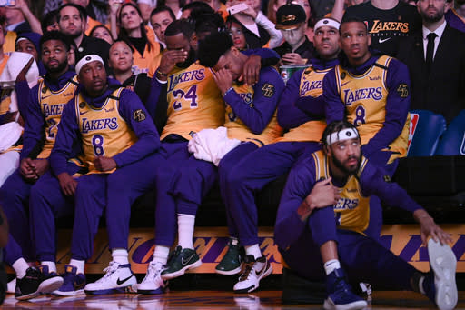 Los Angeles Lakers' LeBron James, center, and Quinn Cook wipe their faces while watching a video tribute to Kobe Bryant, before the Lakers' NBA basketball game against the Portland Trail Blazers in Los Angeles, Friday, Jan. 31, 2020. (AP Photo/Kelvin Kuo)