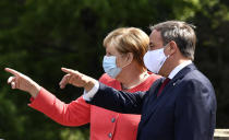 FILE - In this Aug. 18, 2020 file photo, German chancellor Angela Merkel, left, wears a face mask due to the coronavirus pandemic as she meets Governor Armin Laschet, right, during her visit at Germany's most populated federal state North Rhine-Westphalia in Duesseldorf, Germany. The coronavirus pandemic is colliding with politics as Germany embarks on its vaccination drive and one of the most unpredictable election years in its post-World War II history. (AP Photo/Martin Meissner, File)