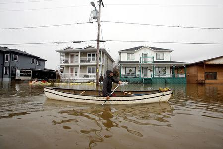 A man paddles a canoe in a flooded residential area in Gatineau, Quebec, Canada, May 7, 2017. REUTERS/Chris Wattie