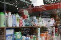"""The corporate logo of the Venezuela state oil company PDVSA is seen reflected in the window of a """"bodegon"""" at a gas station in Caracas"""