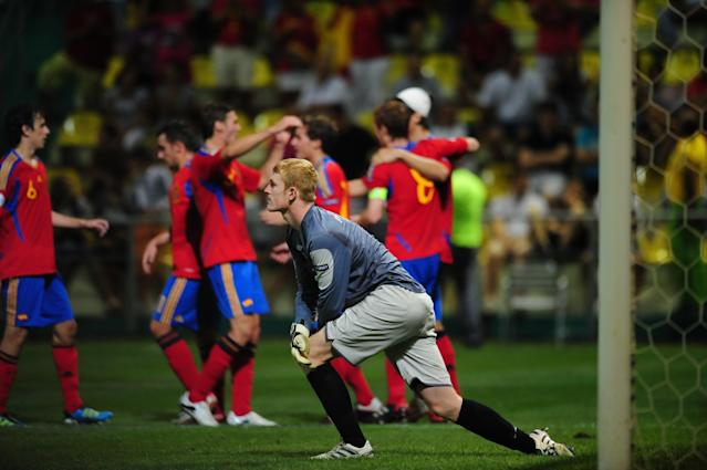 Spain team players celebrate their 5-0 score against Ireland as Irish goalkeeper Aaron McCarey (C) stretches during their UEFA European Under-19 Championship football match, near the village of Chiajna village, outside of Bucharest, on July 29, 2011. AFP PHOTO/DANIEL MIHAILESCU (Photo credit should read DANIEL MIHAILESCU/AFP/Getty Images)