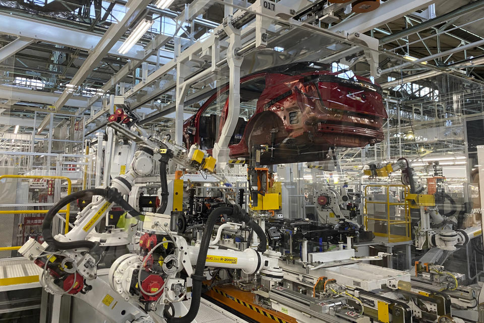 """Robotic arms put in the electric vehicle powertrain into the Ariya model in the assembly line at Nissan's Tochigi plant in Kaminokawa town, Tochigi prefecture, Japan, Friday, Oct. 8, 2021. Nissan's """"intelligent factory"""" hardly has any human workers. The robots do the work, including welding and mounting. They do the paint jobs and inspect their own paint jobs. (AP Photo/Yuri Kageyama)"""