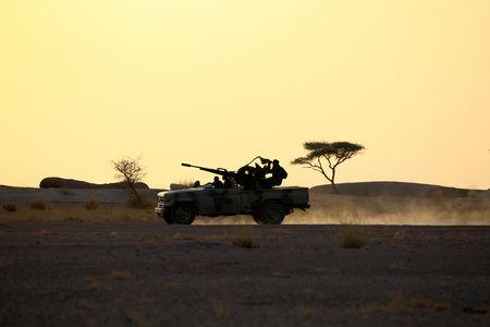 FILE PHOTO: The Polisario Front soldiers drive a pick-up truck mounted with an anti-aircraft weapon at sunset in Bir Lahlou, Western Sahara, Sept 9, 2016. REUTERS/Zohra Bensemra/File Photo