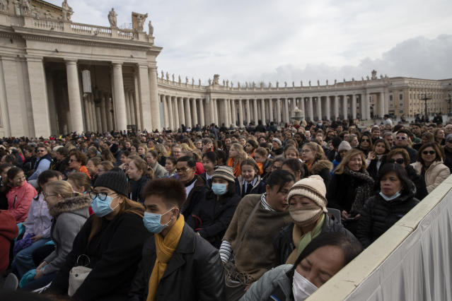 Faithful wear face masks as they wait for Pope Francis arrival in St. Peter's Square at the Vatican for his weekly general audience, Wednesday, Feb. 26, 2020. (AP Photo/Alessandra Tarantino)
