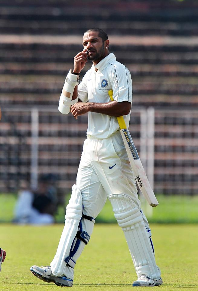 Indian cricketer Shikhar Dhawan walks out of the ground after a ball hit him on the face during the final day of the three-day practice cricket match between Australia and Indian Board President's XI in Chandigarh on September 27, 2010. The match ended in a draw.  AFP PHOTO/Dibyangshu SARKAR