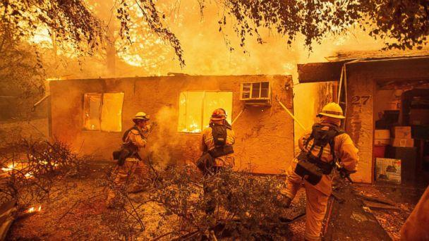 PHOTO: Firefighters push down a wall while battling a fire in an apartment complex in Paradise, Calif., Nov. 09, 2018. (Josh Edelson/AFP/Getty Images)