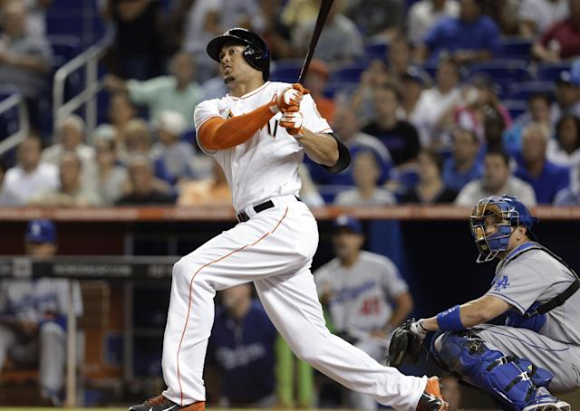 Miami Marlins' Giancarlo Stanton watches his solo home run in the first inning in front of Los Angeles Dodgers catcher A.J. Ellis during a baseball game, Wednesday, Aug. 21, 2013, in Miami. (AP Photo/Lynne Sladky)