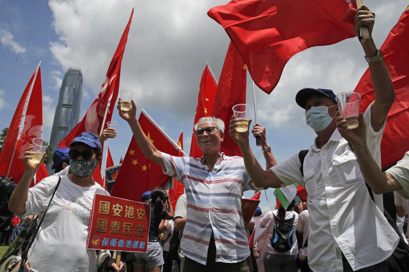 "Pro-China supporters holding Chinese national flags, toast during a rally to celebrate the approval of a national security law for Hong Kong, in Hong Kong, Tuesday, June 30, 2020. Hong Kong media are reporting that China has approved a contentious law that would allow authorities to crack down on subversive and secessionist activity in Hong Kong, sparking fears that it would be used to curb opposition voices in the semi-autonomous territory. A placard reads ""Country secure, Hong Kong secure, the country prospects, the people at peace"". (AP Photo/Kin Cheung)"