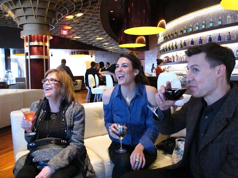 In this March 28, 2012, photo, Sheri Frankel, left, Ashley Frankel, center, both of Margate, N.J., and Todd Gordon, right, of Atlantic City, N.J., enjoy drinks at Revel, the Atlantic City casino that had its first test night on March 28. The $2.4 billion resort opens to the public on Monday, April 2. (AP Photo/Wayne Parry)
