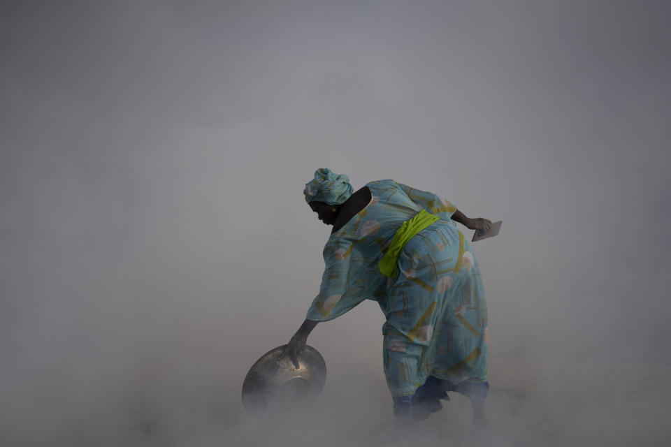 Ndeye Yacine Dieng drops embers over peanut shells covering fish as she walks amidst the smoke on Bargny beach, some 35 kilometers (22 miles) east of Dakar, Senegal, Wednesday April 21, 2021. Since her birth on Senegal's coast, the ocean has always given Ndeye Yacine Dieng life. Her grandfather was a fisherman, and her grandmother and mother processed fish. Like generations of women, she helps support her family in the small community of Bargny by drying, smoking, salting and fermenting the catch brought home by male villagers. They were baptized by fish, these women say. (AP Photo/Leo Correa)