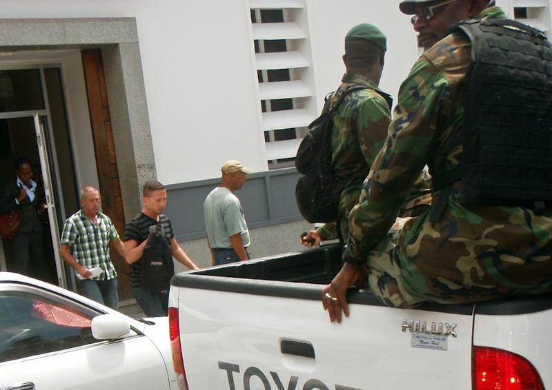 Dennis Jay Mayer, 43, second from left, and John Robert Hart, 41, third from left, both of Palm Springs, California, leave a bank office as police officers wait to escort them back to court, in Roseau, Dominica, Thursday March 22, 2012. The two Southern California men have pleaded guilty to indecent exposure in Dominica following their arrest during a stop on a gay cruise of the Caribbean. Police said the men were seen having sex on a deck of a Celebrity Summit cruise ship by someone on the dock. (AP Photo/Carlisle Jno-Baptiste)