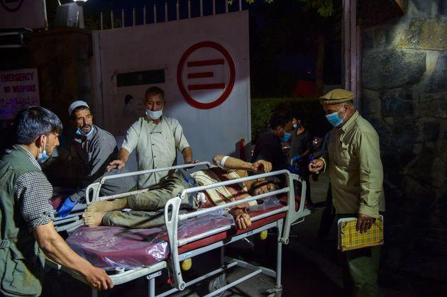 EDITORS NOTE: Graphic content / Medical and hospital staff bring an injured man on a stretcher for treatment after two powerful explosions, which killed at least six people, outside the airport in Kabul on August 26, 2021. (Photo by Wakil KOHSAR / AFP) (Photo by WAKIL KOHSAR/AFP via Getty Images) (Photo: WAKIL KOHSAR via Getty Images)