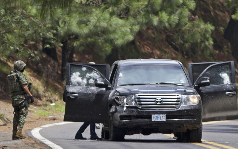 FILE - In this Aug. 24, 2012 file photo, Mexican military personnel check a vehicle in which two United States government employees were shot on the highway leading to the city of Cuernavaca, near Tres Marias, Mexico. Mexican prosecutors on Friday, Nov. 9, 2012, charged 14 federal police officers with trying to kill two CIA officers and a Mexican navy captain in the August ambush.  (AP Photo/Alexandre Meneghini, File)