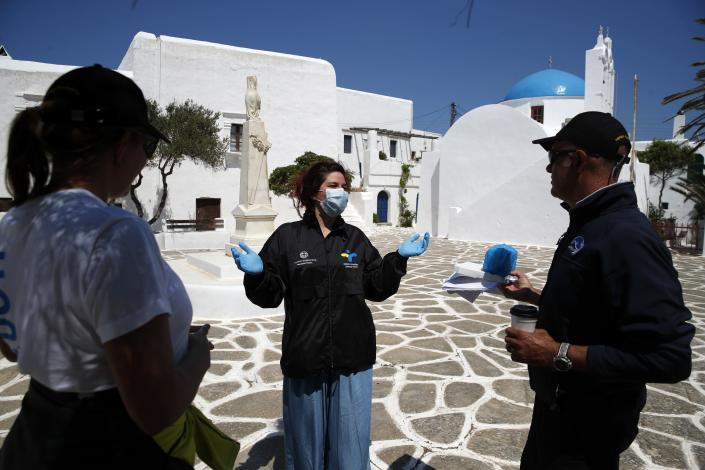 In this Monday, May 25, 2020 photo, a doctor of the Public Health Organization (EODY), center, speaks with the members of the non-for-profit Organization Symplefsi after she has tested the local residents for the new coronavirus, on the Aegean Sea island of Sikinos, Greece. Using dinghies, a GPS, and a portable refrigerator, state doctors have launched a COVID-19 testing drive on islands in the Aegean Sea ahead of the holiday season. The first round of testing was completed after trips to the islands of Milos, Kimolos, Folegandros, and Sikinos. (AP Photo/Thanassis Stavrakis)