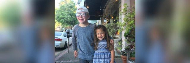 Brother and sister hugging and smiling at camera. They both have Down syndrome.