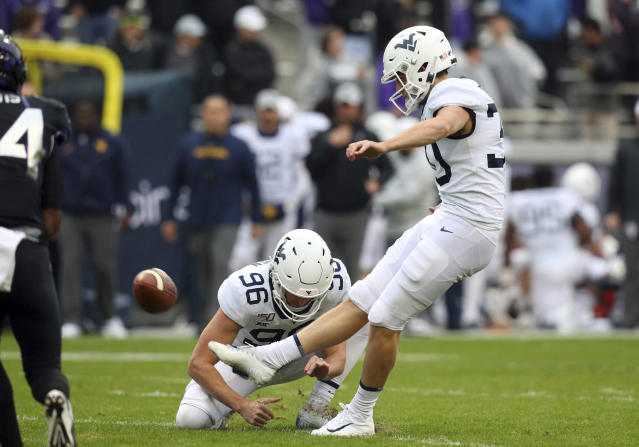 West Virginia punter Josh Growden (96) holds for place kicker Evan Staley (30) who kicks an extra point against TCU in the first half of an NCAA college football game Friday, Nov. 29, 2019, in Fort Worth, Texas. (AP Photo/Richard W. Rodriguez)