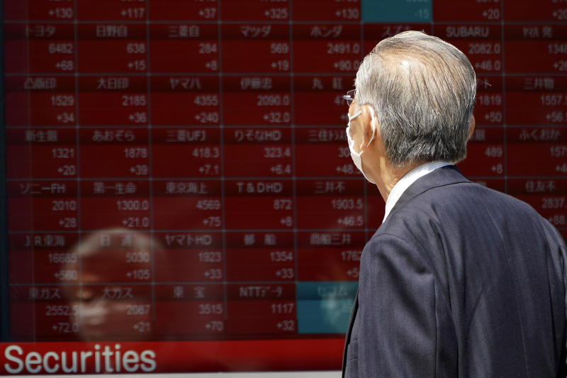 A man wearing a face mask to help curb the spread of the coronavirus looks at an electronic stock board showing Japan's Nikkei 225 index at a securities firm in Tokyo Friday, May 8, 2020. Asian shares surged Friday on optimism the worst of the economic fallout from the pandemic may be over, as Wall Street logged its biggest rally in a week. (AP Photo/Eugene Hoshiko)