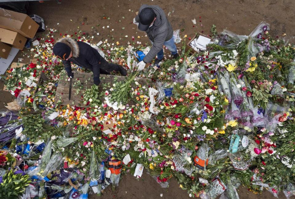 Overhead view of two people surrounded by flowers, chopping them up on a wooden table.