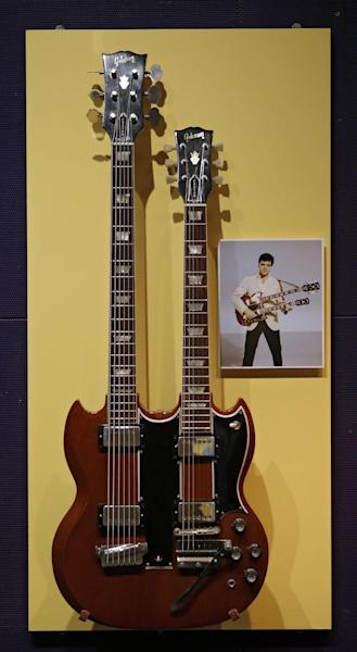 In this Nov. 25, 2013 photo, a rare Gibson double-necked guitar belonging to Elvis Presley hangs at the Rock and Roll Hall of Fame and Museum in Cleveland. (AP Photo/Mark Duncan)