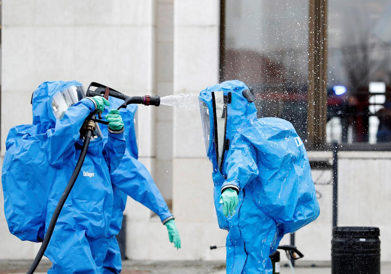 Members of the police's chemical unit clean themselves after inspecting a substance spilled by an unknown person in front of the Slovak parliament in Bratislava, Slovakia March 23, 2018.  REUTERS/David W Cerny     TPX IMAGES OF THE DAY