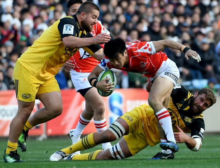 Sunwolves' Takaaki Nakazuru runs with the ball past Hurricanes' Dane Coles (L) and Callum Gibbins during their Super Rugby match, at the Prince Chichibu Memorial stadium in Tokyo, on February 25, 2017
