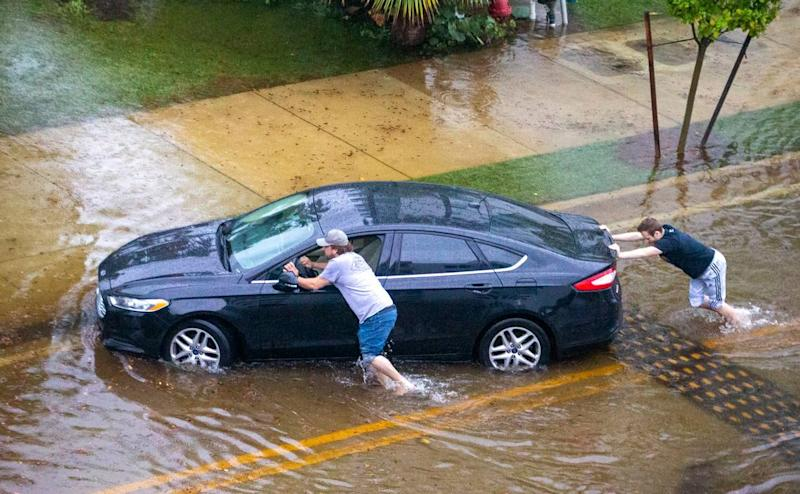 Two men push a stranded car through a flooded road after heavy rains at North Bay Road and 180th Drive in Sunny Isles Beach on Monday, May 25, 2020.